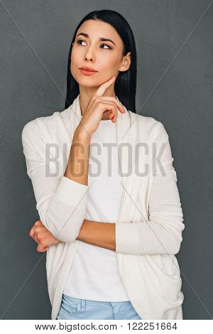 Thoughtful beauty. Beautiful young pensive woman keeping hand on chin and looking away while standing against grey background