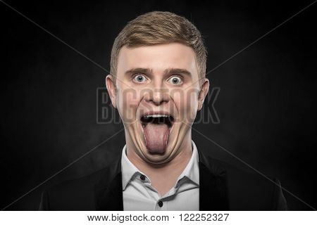 Young businessman with a funny face and his tongue out over dark background.