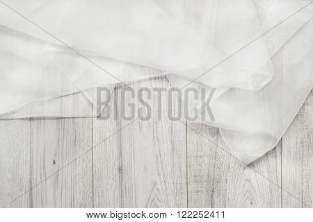 White folded chiffon on white wooden background