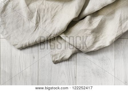 Beige folded linen on white wooden floor as a background