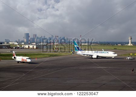 CALGARY, CANADA - JULY 18: Two commercial airliners sit on the tarmac of Calgary International Airport YYC with the city's downtown skyline in the background July 18 2014. The airport serves as headquarters for WestJet and as a hub airport for Air Canada.