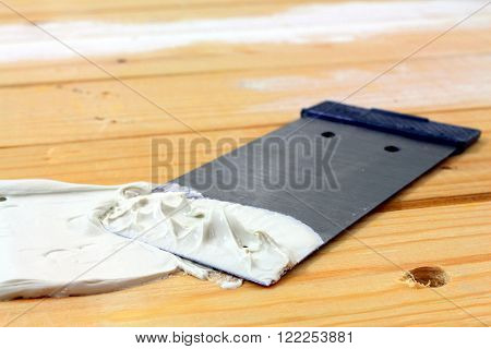 a spatula with spatula masse on wood