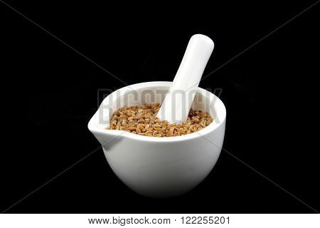 a white mortar with cereal on black