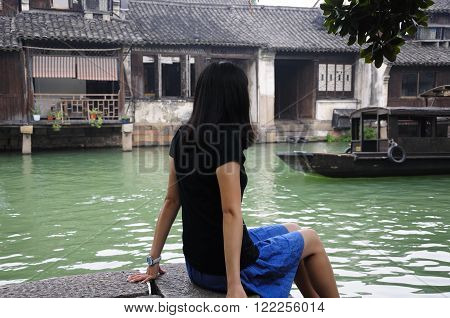An Chinese woman sitting on a the edge of a water canal in Tongxiang's Wuzhen west scenic area located in Zhejiang province China as a boat moves by.