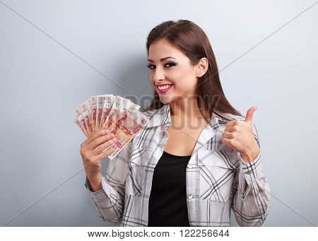 Happy Young Casual Woman In Glasses Holding Roubles And Showing Thumb Up Sign With Toothy Smiling