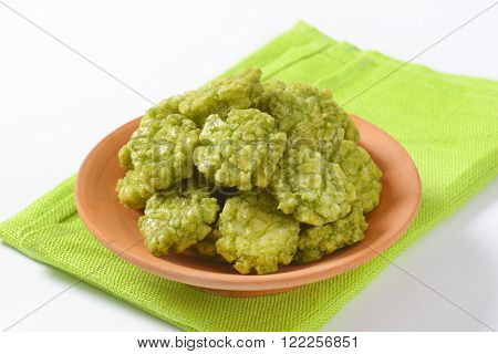 bowl of wasabi crackers on green place mat - close up