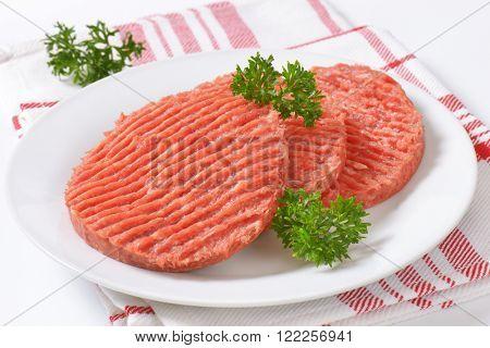plate of raw hamburger patties on checkered dishtowel - close up