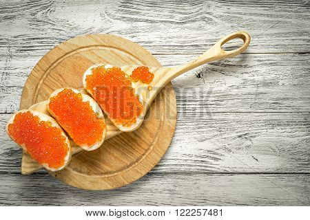 Sandwiches with salmon red caviar on a cutting boards and natural wooden background with copy space