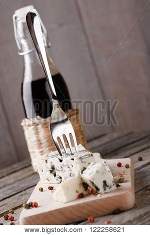 Vertical askew photo of  blue cheese portion placed on wooden board with colour pepper seeds around. Bottle of wine is next to cheese and small fork is stuck inside. All is on old grey table.