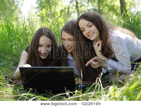 three students relax and laughing on the grass in the park