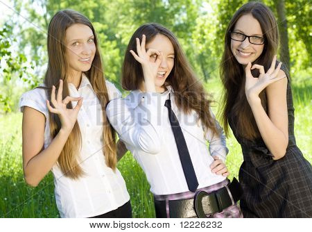 three happy student girl give the sign okey in the park