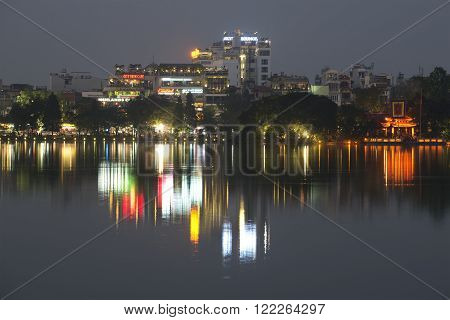 HANOI, VIETNAM - DECEMBER 13, 2015: Evening panorama of Hoan Kiem lake. Modern buildings reflected in the water