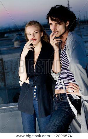 stylish couple smoking outdoor on the night