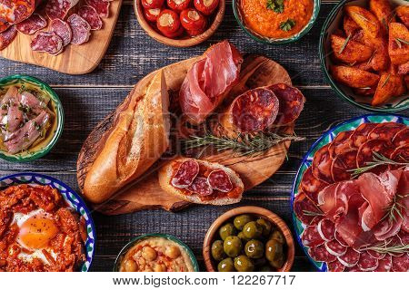 Typical spanish tapas concept. Concept include variety slices jamon chorizo salami bowls with olives peppers anchovies spicy potatoes mashed chickpeas on a wooden table.
