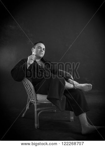 Smoking man in a bathrobe sitting in the chair