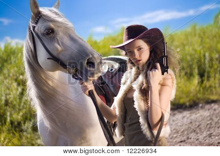 young cowgirl with gun outdoor
