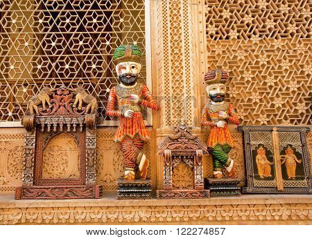 JAISALMER, INDIA - February 1 2015: Wooden figures of Rajasthan men and other souvenirs waiting for customers on the flea market on February 1, 2015. Jaisalmer lies in the Thar Desert and has a population of 78000