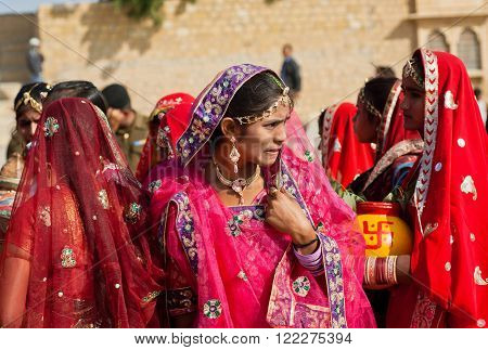 JAISALMER. INDIA - February 1 2015: Woman thinking about something in a crowd of friends dressed in sari on the Desert Festival on February 1, 2015. Every winter Jaisalmer takes the Desert Festival of Rajasthan