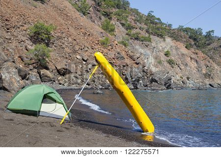 Camping on the seashore, the tent is on the beach, kayak stands next to the tent.