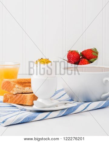 Soft boiled egg and toast served with coffee and Juice.