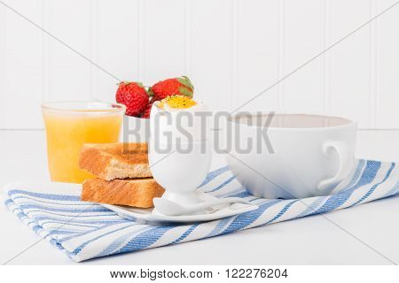 Soft boiled egg with toast served with coffee and juice.