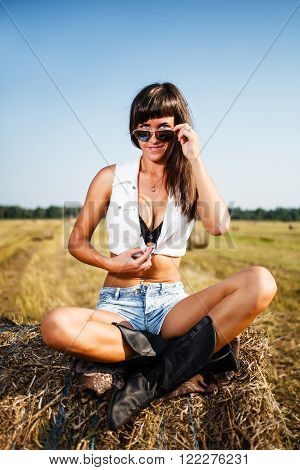 Sexy brunette sitting on a straw bale.