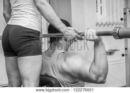 Gym man exercising with his personal trainer.Man with his personal fitness trainer in the gym exercising with athletic Rod.Sport, power,dumbbells tension,exercise - the concept of a healthy lifestyle.