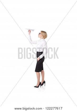 Young pretty businesswoman with paper plane ready to throw it. Side view. Isolated. Concept of starting a new project.