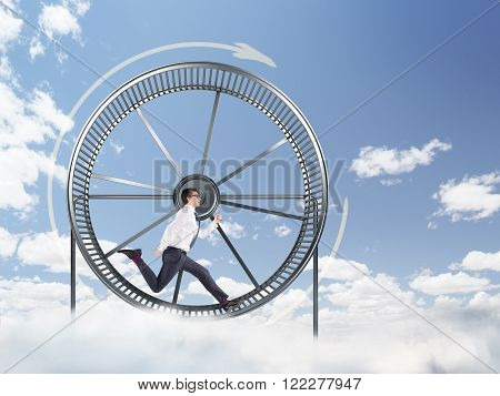 Young businessman running in spinning wheel. Blue sky at background. Concept of hard work.