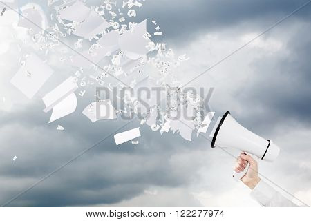 Hand holding white loudspeaker paper and letters flying from it. Grey sky at background. Concept of informing.