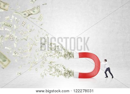 Businessman with magnet pulling dollars. Concrete background. Concept of attracting money.