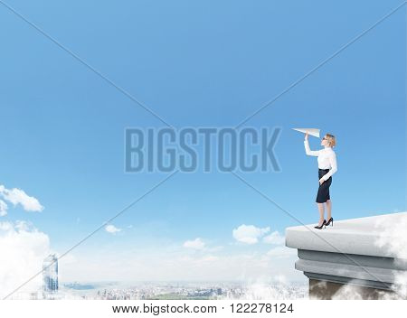 Businesswoman standing on roof throwing paper plane city view blue sky at background. Concept of starting new project.