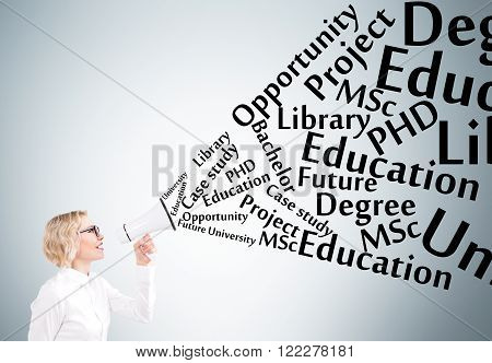 Businesswoman holding white loudspeaker many education words from it. Grey background. Concept of informing.