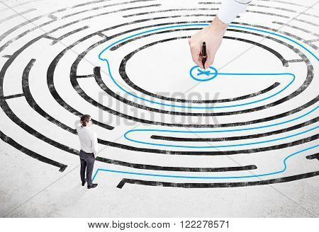 Businessman with hand on head standing on white floor in front of painted labyrinth hand drawing blue way out. Concept of finding solution.