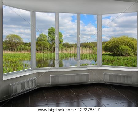 modern window overlooking the summer bog with bushes