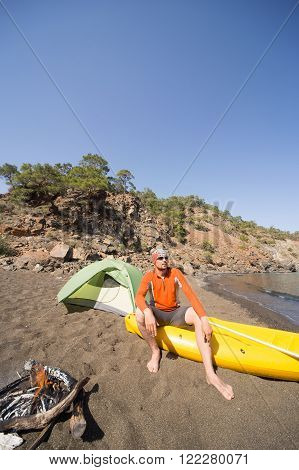 The man on the beach with kayak and tent on a sunny day.