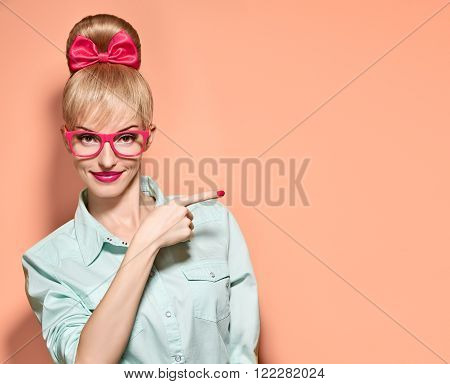 Beauty fashion woman in stylish glasses shows finger. Attractive happy blonde hipster girl smiling, emotional. Confidence, success, Pinup hairstyle. Unusual playful, expression nerd. Vintageon pink