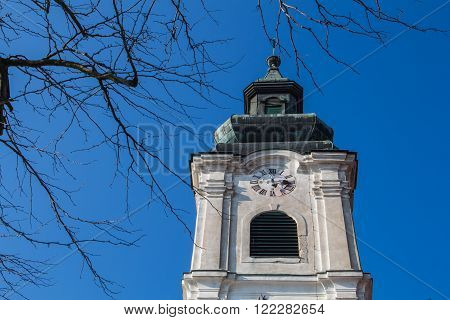 Twigs of the tree in the foreground. Tower of the Church of Saint Cross in Devin Bratislava Slovakia. Bright blue sky.