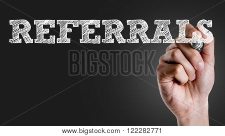 Hand writing the text: Referrals