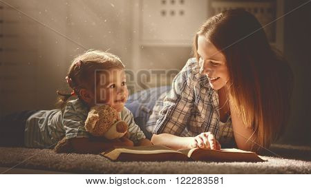 happy family mother and daughter read a book in the evening at home