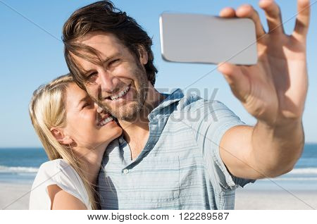 Happy smiling couple on the beach taking photo of themselves with smart phone. Young cheerful couple taking a selfie. Young couple embracing and capturing romantic moments with cellphone.