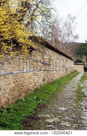 Stone Wall and yellow flowers. Street with cobble stones of folk museum Zheravna village in Bulgaria. Mountain village.