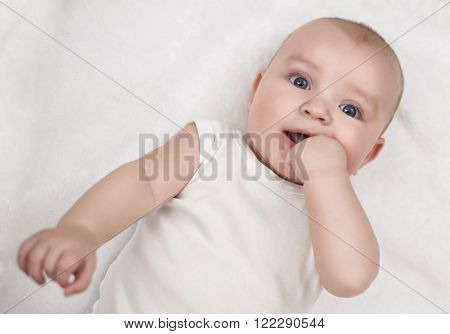 Bright closeup portrait of adorable baby.Funny laughing baby lying on back and looking at camera.