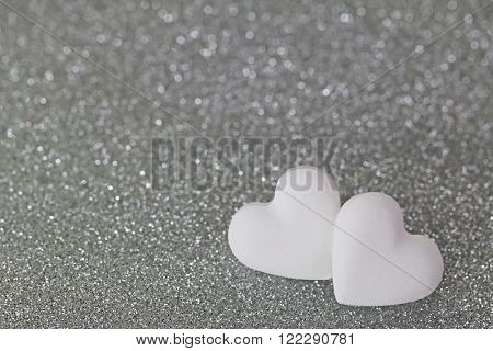 Soft focus of 2 heart shaped candy pills on silver glittery background with shallow depth of field with copyspacesparkling