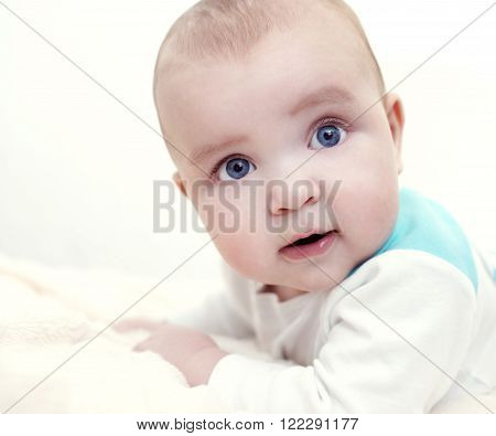 A cropped shot of an adorable baby boy lying on a blanket.Close up headshot of a caucasian baby boy.