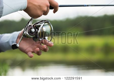 Fisherman on the river bank in sunglasses.Fisherman in his hand holding spinning. Fishing, spinning reel, fish, Breg rivers. - The concept of a rural getaway. Article about fishing. ** Note: Shallow depth of field