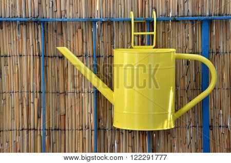 Yellow metal watering can (pot) hang on balcony railing bamboo fence in background