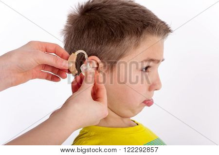 Small boy trying his first hearing aid and not too happy with it. Focused on the hand and the hearing aid.