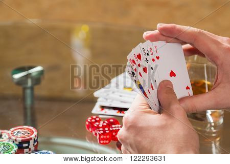 The concept of card games. Man playing poker at the poker table.