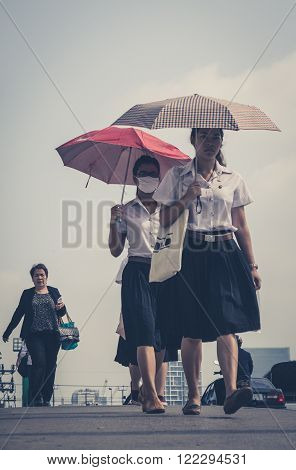 Bangkok Thailand - March 05 2014: Street portrait of two girls with umbrellas one wearing a mask. Bangkok Air pollution reaches a critical level.